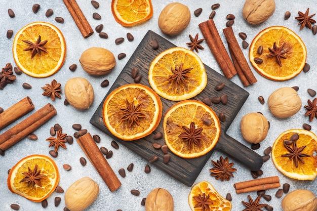 Świąteczna kompozycja z suszonymi pomarańczami, cynamonem, anyżem i orzechami na szarym betonowym tle.