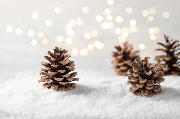 Świąteczna kompozycja z szyszkami, śniegiem i niewyraźnymi lampkami choinkowymi