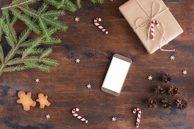 Świąteczna kompozycja z telefonem komórkowym, prezentem i piernikowym człowiekiem na drewnianym ciemnym tle z szyszkami, gałęzie jodły na drewnianym biurku, płaski widok i widok z góry, kopia przestrzeń