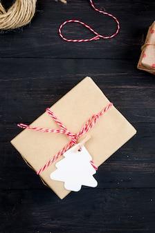 Świąteczna kompozycja z wieloma rzemieślniczymi pudełkami na prezenty, gałązkami jodły i piernikami