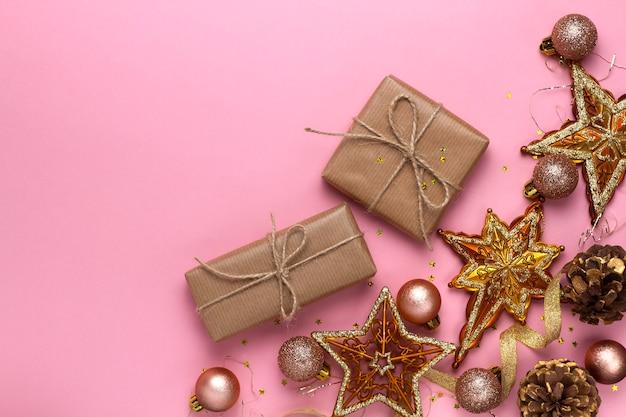Świąteczna kompozycja z zabawkami, prezentami, gwiazdami, kulkami i świecidełkiem na różowym tle. widok płaski, widok z góry.