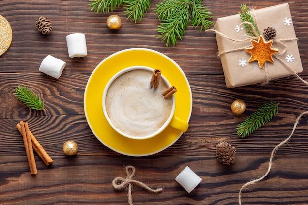 Świąteczna kompozycja z żółtą filiżanką cappuccino i pudełkiem w stylu retro