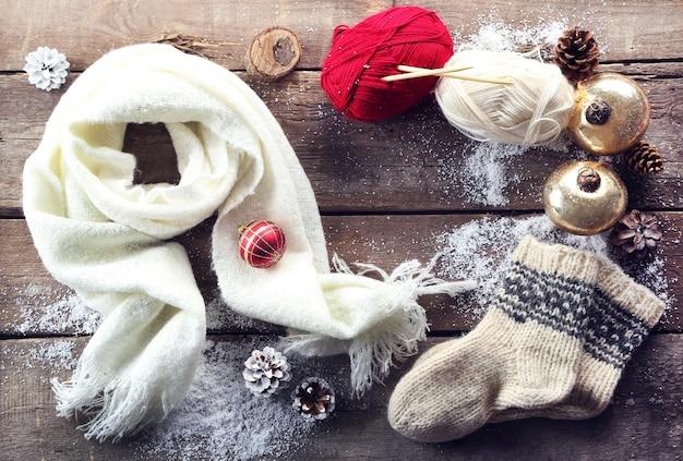 Świąteczna kompozycja ze skarpetkami, szalikiem i dekoracjami na drewnianym stole