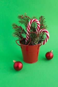 Świąteczna kompozycja ze świerkowymi gałązkami w czerwonym wiadrze na zielonym tle