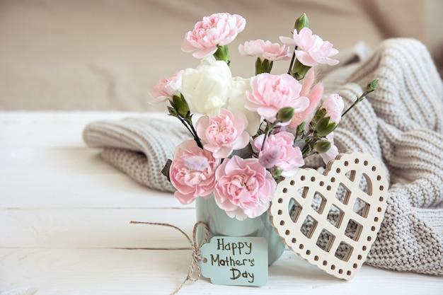 Świąteczna kompozycja ze świeżymi kwiatami w wazonie, elementami dekoracyjnymi i życzeniem szczęśliwego dnia mamy na kartce