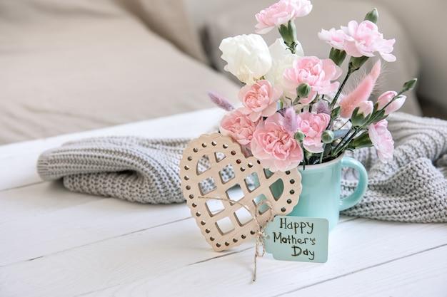 Świąteczna kompozycja ze świeżymi kwiatami w wazonie, elementami dekoracyjnymi i życzeniem szczęśliwego dnia mamy na pocztówce.
