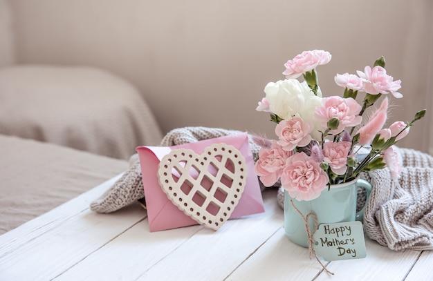 Świąteczna kompozycja ze świeżymi kwiatami w wazonie, elementami dekoracyjnymi i życzeniem wesołych świąt wielkanocnych na pocztówce.