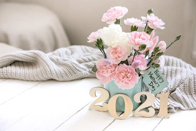 Świąteczna kompozycja ze świeżymi kwiatami w wazonie, rok 2021 i życzeniem szczęśliwego dnia matki na pocztówce.