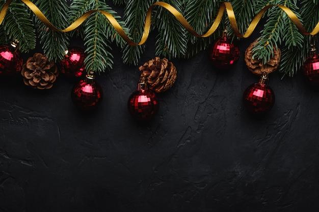 Świąteczna kompozycja ze złotą wstążką, czerwonymi ornamentami i bombkami, szyszkami jodły i sosny