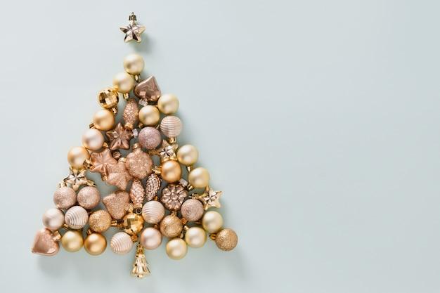 Świąteczna kompozycja ze złotymi błyszczącymi bombkami w kształcie drzewka