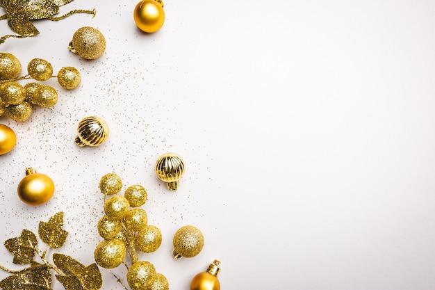 Świąteczna kompozycja ze złotymi dekoracjami na białym tle z miejscem na kopię