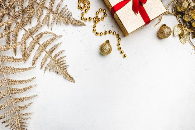 Świąteczna kompozycja ze złotymi dekoracjami na białym tle
