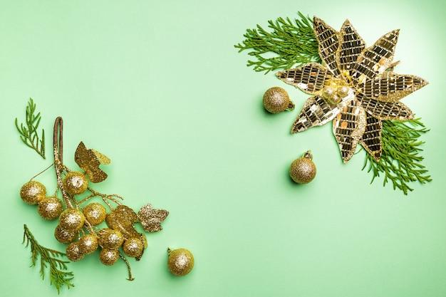 Świąteczna kompozycja ze złotymi dekoracjami na zielonym tle z miejscem na kopię