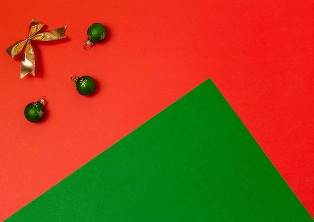 Świąteczna kompozycja zielone kulki i złota kokardka na tle czerwono-zielonego koloru