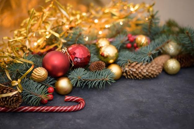 Świąteczna kompozycja złotych i czerwonych kulek, cukierków, girland, gałęzi jodły, szyszek jodły.