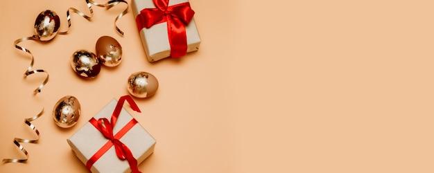 Świąteczna kompozycja złotych jaj i pudełek z czerwoną wstążką