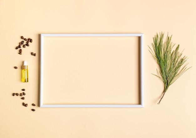 Świąteczna koncepcja aromaterapii i spa z białą pustą ramą i małą szklaną butelką z aromatycznym olejkiem cedrowym z iglastych spa, gałęzi, orzechów. widok z góry, skopiuj przestrzeń wewnątrz ramki.