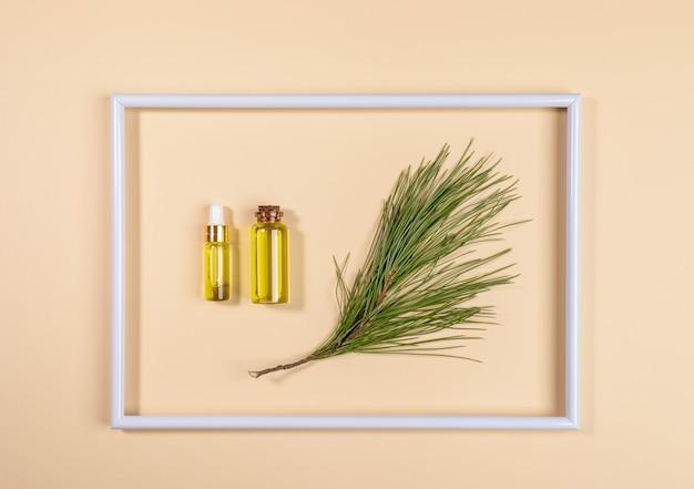 Świąteczna koncepcja aromaterapii i spa z małymi szklanymi butelkami z aromatycznym olejkiem eterycznym z iglastego cedru wewnątrz białej ramki na beżowym tle. widok z góry.