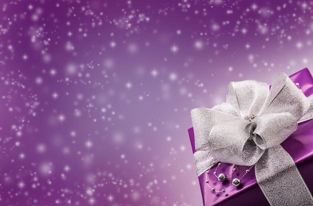 Świąteczna koncepcja bokeh z fioletowym prezentem w prawym dolnym rogu i ilustrowanymi płatkami śniegu w tle.