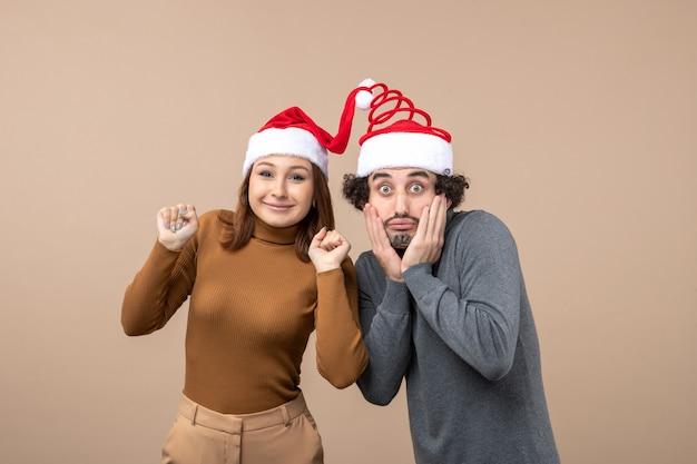 Świąteczna koncepcja świąteczna i imprezowa - szczęśliwa piękna, zaskoczona młoda para ubrana w zjednoczonego świętego mikołaja