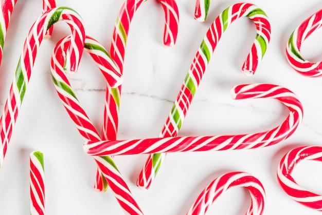 Świąteczna koncepcja świąteczna, wiele tradycyjnych noworocznych słodyczy trzciny cukrowej na stole z białego marmuru. , widok z góry copyspace