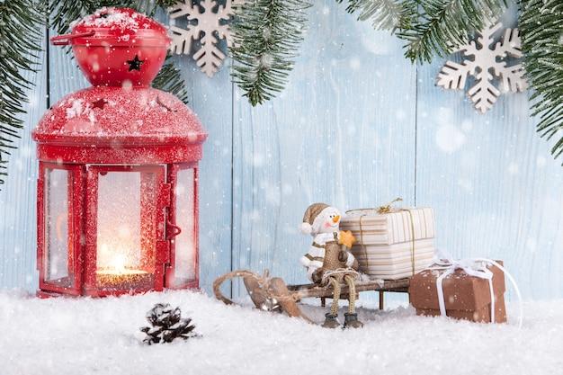 Świąteczna koncepcja z uśmiechniętym bałwanem, pudełkami na prezenty i świąteczną latarnią