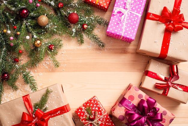 Świąteczna kopia przestrzeń z ozdobioną gałęzią jodły w rogu i kolorowymi prezentami wokół