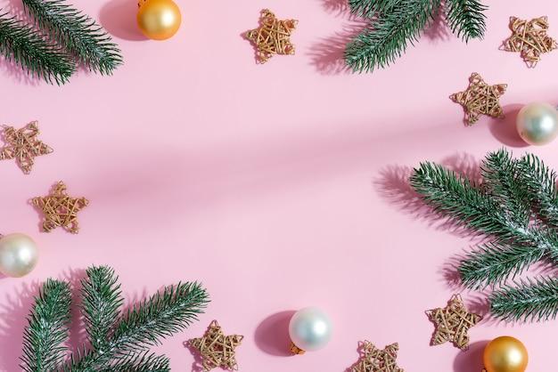 Świąteczna, kreatywna oprawa świąteczna z wiecznie zielonych gałązek jodły, błyszczących gwiazd, małych złotych i srebrnych kulek na pastelowym różu. leżał na płasko.