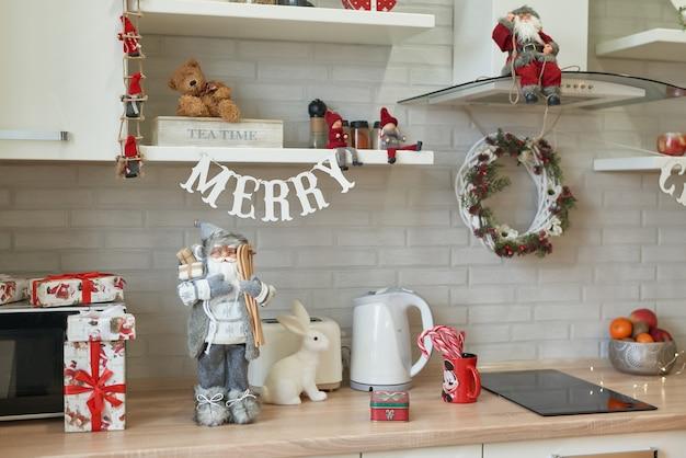 Świąteczna kuchnia w stylu loftu, przybory kuchenne. wnętrze lekka kuchnia z bożonarodzeniowym wystrojem i drzewem. nowoczesny design kuchni, białe meble kuchenne. świąteczny nastrój.