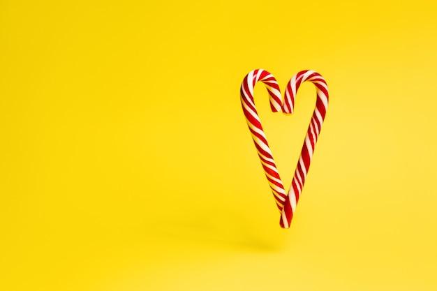 Świąteczna laska w kształcie serca na żółtym tle.