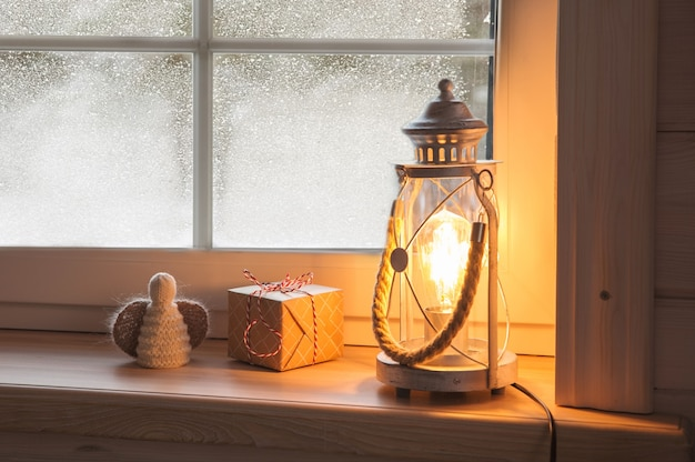 Świąteczna latarnia bożonarodzeniowa, prezenty i anioł na drewnianym parapecie w zimie w pomieszczeniu. dekoracja świąteczna w stylu skandynawskim