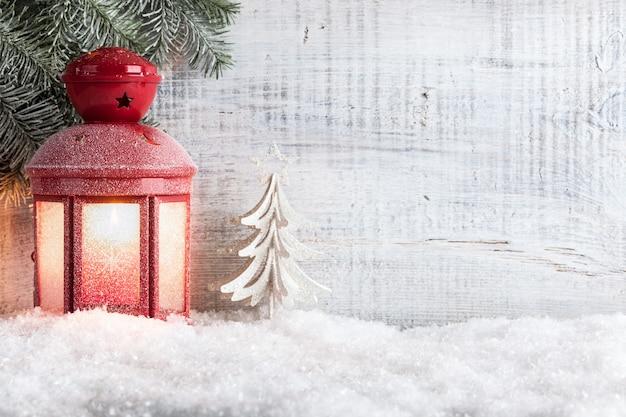 Świąteczna latarnia świeca na śniegu i drewnianym tle