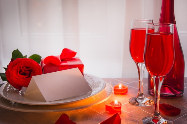 Świąteczna lub romantyczna kolacja z czerwoną różą i szampanem