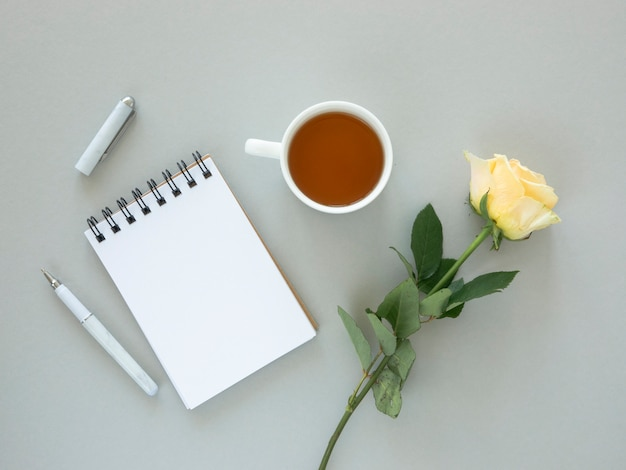 Świąteczna makieta pulpitu. kwiat róży, filiżanka herbaty i notes na spirali z miejscem na pozdrowienia. koncepcja wakacji