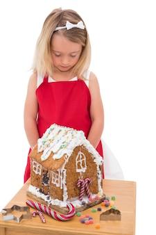 Świąteczna mała dziewczynka robi piernikowemu domowi