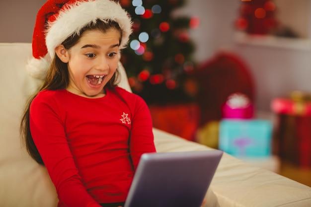 Świąteczna mała dziewczynka używa pastylka komputer osobistego na leżance
