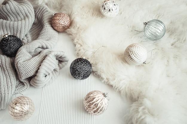 Świąteczna martwa natura z dekoracyjnymi zabawkami i dzianinowym swetrem.