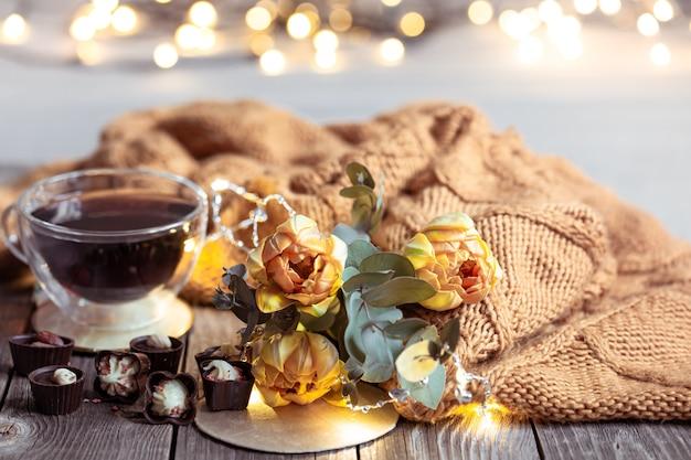 Świąteczna martwa natura z drinkiem w filiżance, czekoladkami i kwiatami na niewyraźnym stole z bokeh.