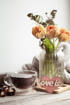 Świąteczna martwa natura z napisem love it, kwiatami w wazonie i filiżanką herbaty oraz detalami dekoracyjnymi.