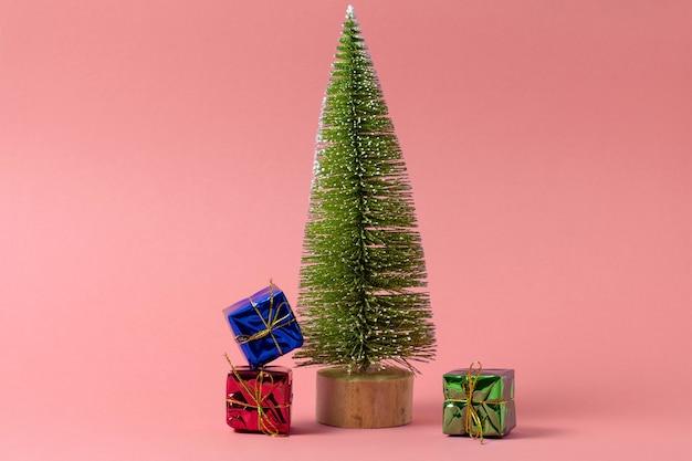 Świąteczna minimalna kartka okolicznościowa z choinką i pudełkami na różowo
