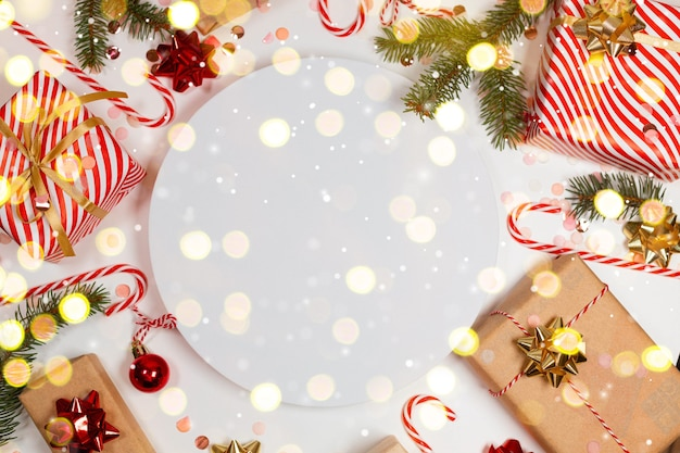 Świąteczna minimalna ramka z pudełkiem, papierowymi dekoracjami, świerkowymi gałęziami i cukierkiem na białym tle. tło wakacje nowy rok. płaski układ, widok z góry, rama