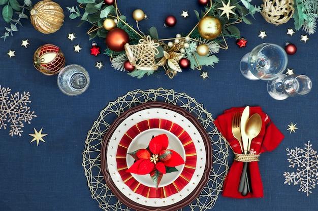Świąteczna nakrycie stołu w kolorach złotym, bordowym i klasycznym niebieskim. leżał płasko, widok z góry na dekoracyjny układ stołu, złote sztućce. tradycyjny świąteczny wystrój na klasycznym niebieskim lnie