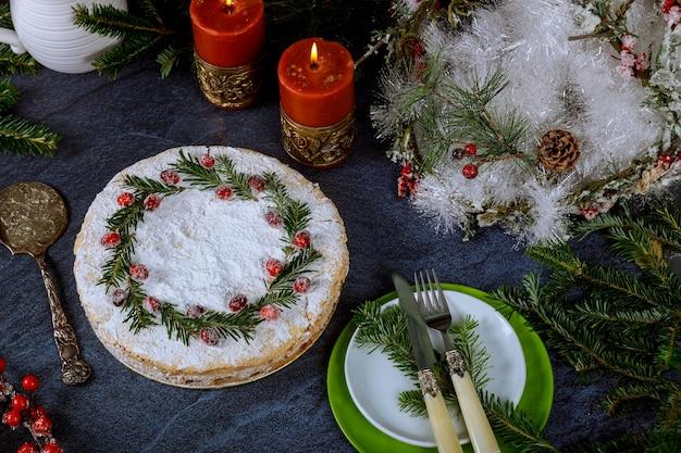 Świąteczna noc z świątecznym ciastem ozdobionym gałązkami żurawiny i sosny