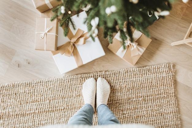 Świąteczna, noworoczna kompozycja z ręcznie robionymi pudełkami na prezenty, gałęziami jodły i kobiecymi stopami