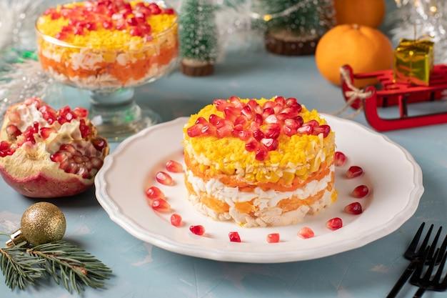 Świąteczna noworoczna sałatka z kurczakiem, jajkiem, marchewką i kukurydzą, ozdobiona gwiazdą z pestek granatu na jasnoniebieskim tle, format poziomy