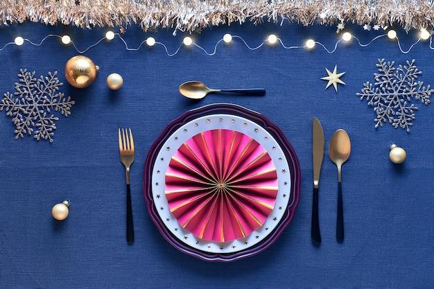 Świąteczna oprawa stołu w kolorze białym, złotym, bordowym z czarno-złotymi sztućcami, na granatowym lnianym obrusie