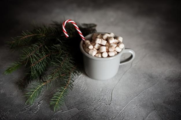Świąteczna oprawa z gorącą czekoladą w fantazyjnym swetrze kubek z piankami, cukierkami, drewnianym jeleniem i świątecznymi lampkami na tle