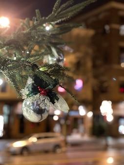 Świąteczna ozdoba z gałęzi drzewa sosnowego w tle nocnego miasta