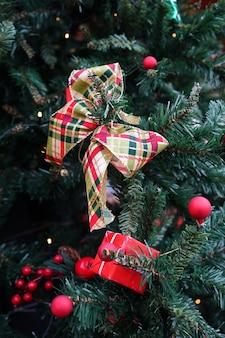 Świąteczna paczka dekoracji, wstążka i czerwone kulki na zielonej choince