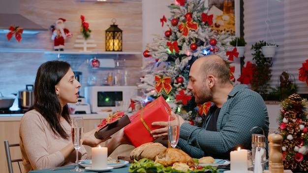 Świąteczna para dająca i otrzymująca prezenty podczas świątecznej kolacji